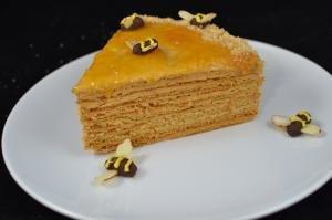 A slice of Russian honey cake on a plate with chocolate bees garnish