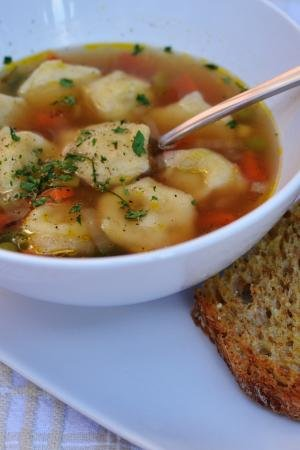 Dumpling (Pelmeni) Soup in a bowl on a plate with 2 bread slice on the plate