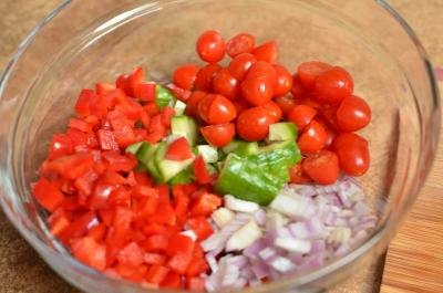 A bowl with baby tomatoes cut in half, diced cucumbers, onions, and bell peppers