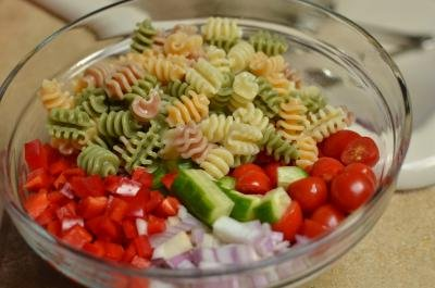 Cooked pasta added to a bowl of cut up veggies