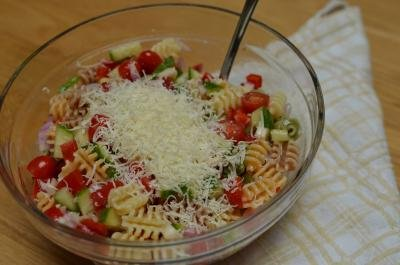 Shredded cheese added to the Italian Pasta Salad in bowl