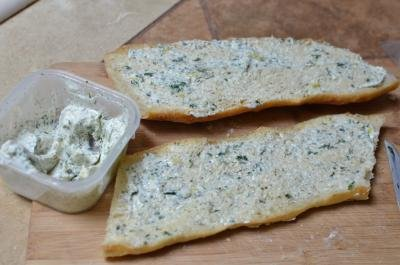Herb butter spread on both sides of the sliced baguette