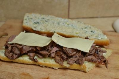 Sandwich being stacked in the following layers; parmesan, steak and havarti cheese