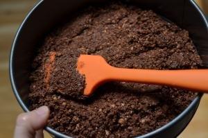 tart crust being pushed dousing into a circular cake baking sheet
