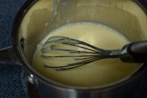 Whisked eggs, condensed milk and milk cooking on stove top