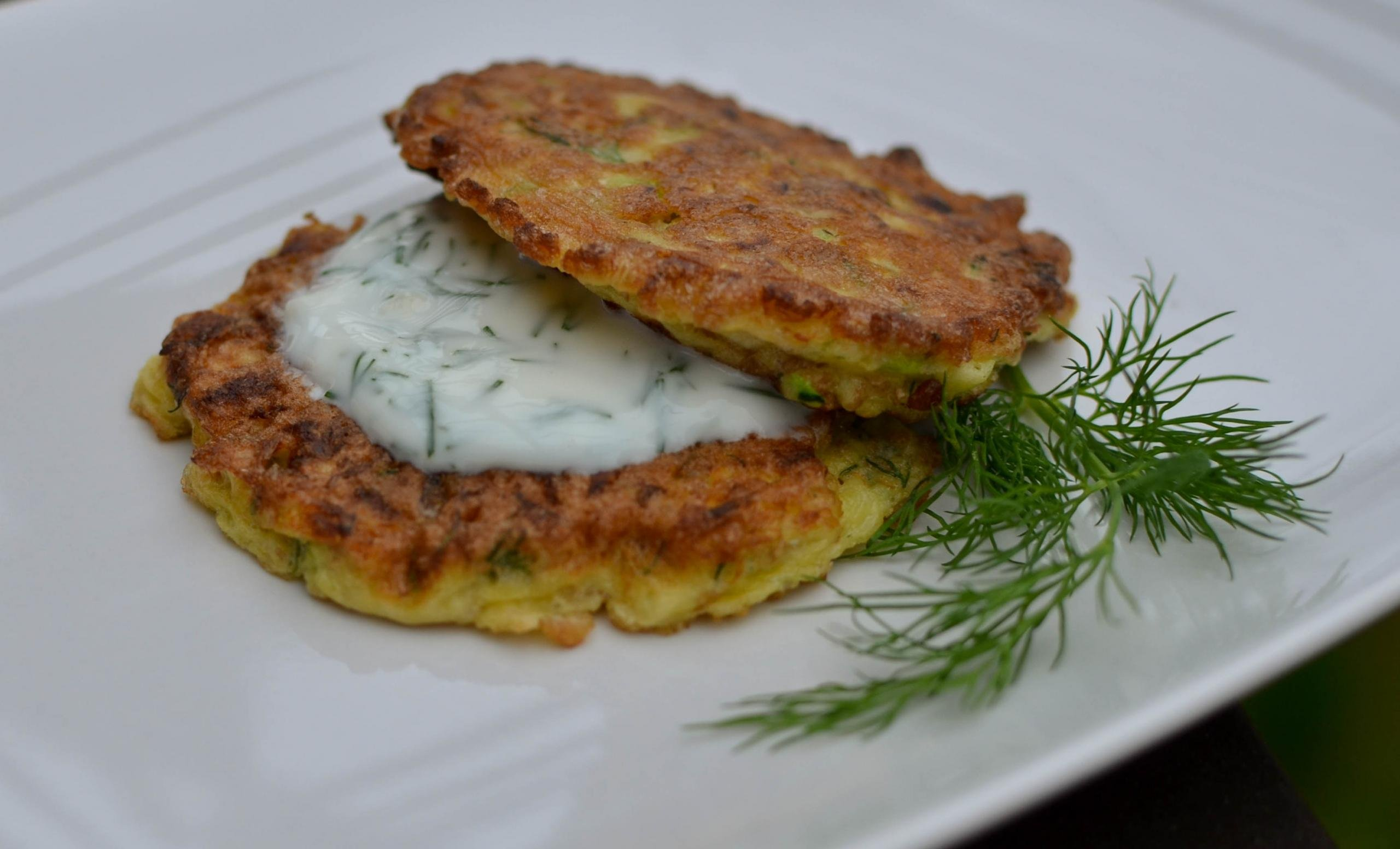 2 Healthy Zucchini Fritters on top of each other with a spread between them