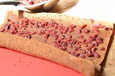 Brunken cherries spread on the unrolled cake