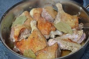 Duck being fried in pan with salt, pepper and bay leaf