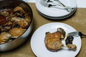 A plate with Roasted Duck with Prunes and a pan full next to it