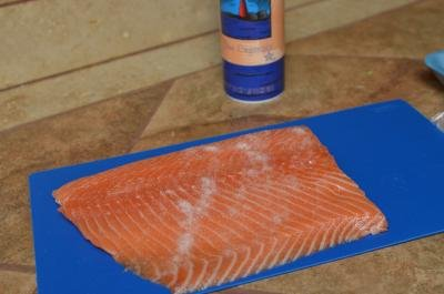 Salmon, on a cutting board, covered in salt