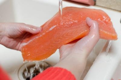 Rinsing salmon under the sink faucet