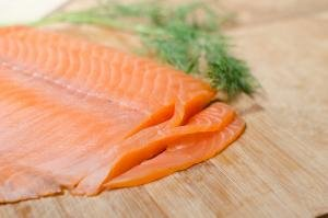 Slicing salmon into thin slices on a cutting board