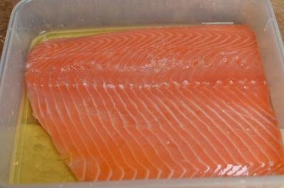 Salmon covered in liquid smoke mixture in plastic tub