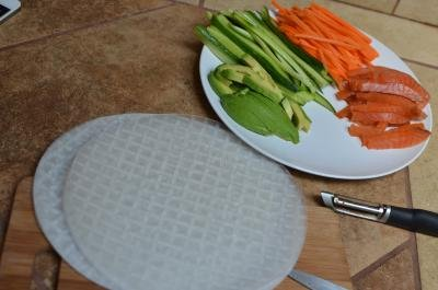 A plate with long thin strips of salmon, carrots, cucumbers, and avocado and rice paper next to the plate