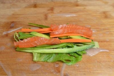 Lettuce, salmon, carrots, cucumbers and avocado in the middle of rice paper