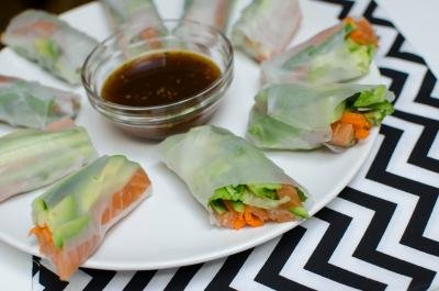Spring Rolls With Salmon cut in half on a plate with sauce in the middle of the plate