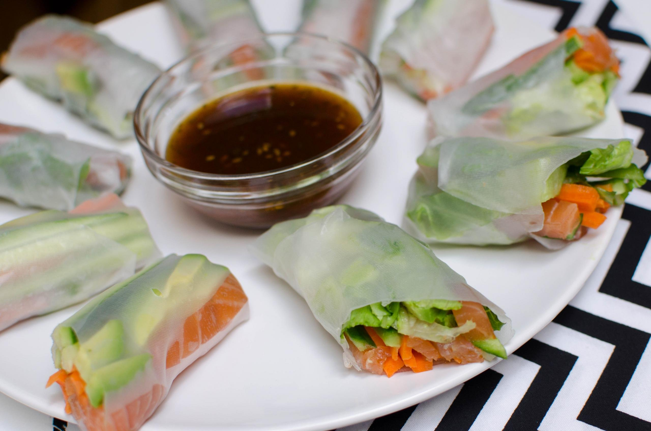 Spring Rolls With Salmon on a plate with little bowl of sauce in the middle of the rolls