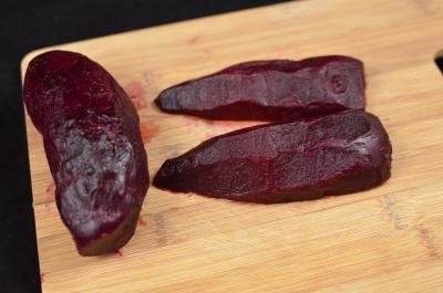 Sliced and peeled beet cut into long vertical slices on a cutting board