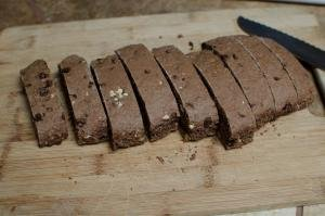 Baked Hazelnut Triple Chocolate Biscotti dough being cut into vertical sections on a cutting board