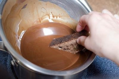 Half of Hazelnut Triple Chocolate Biscotti getting dipped into a bowl of chocolate