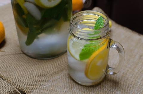 Citrus and Mint Infused Water in a cup with pitcher behind it