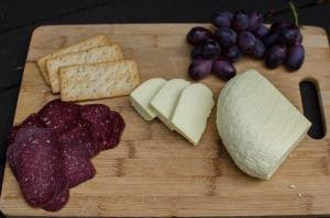 A cheese board with meats, crackers, homemade cheese and grapes