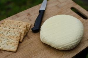 Homemade Cheese on a cutting board with a knife next to it and crackers