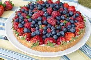A tart covered with strawberries, blueberries and raspberries