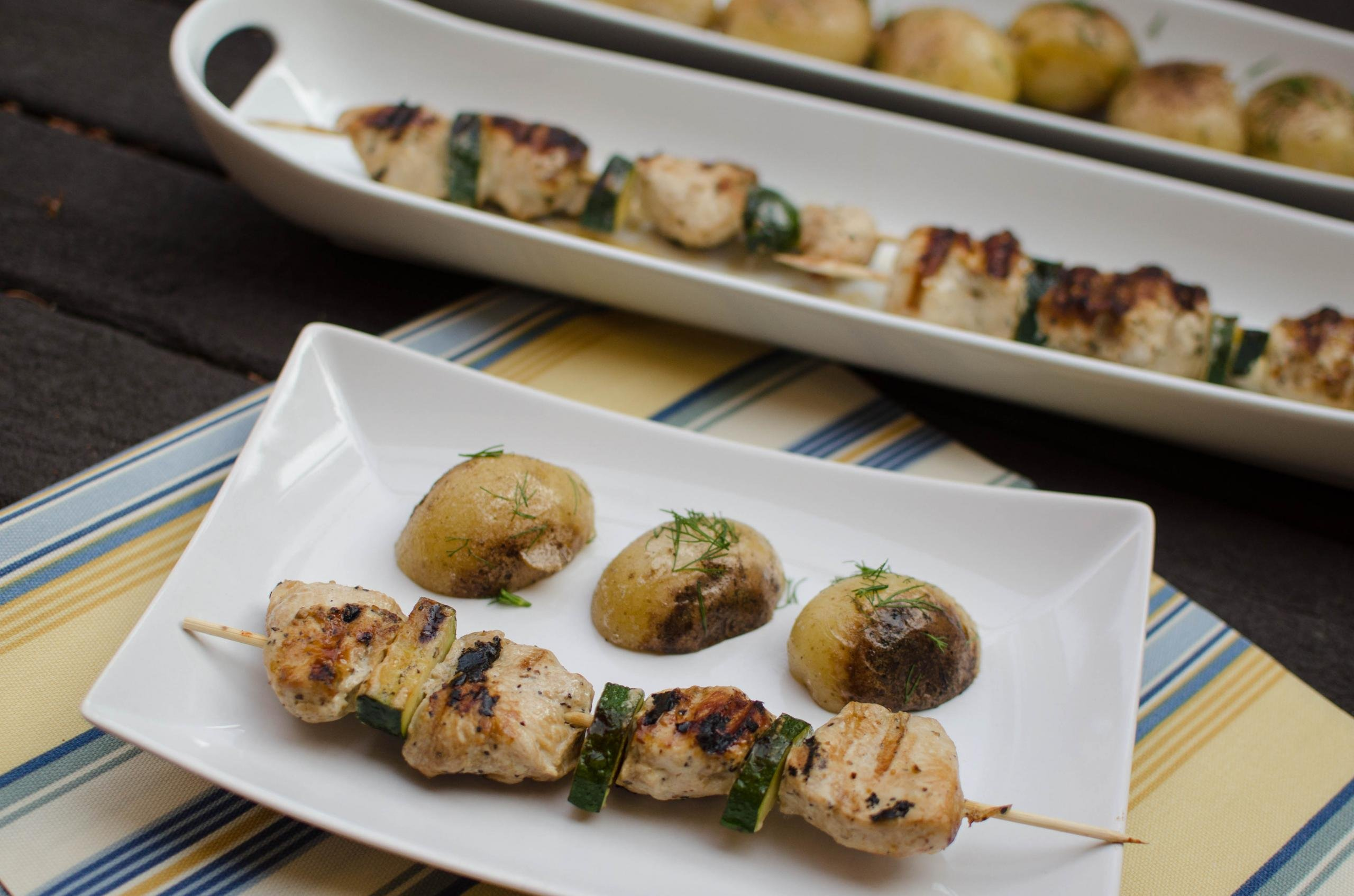 Chicken Kebabs on a plate with oven baked potatoes besides it