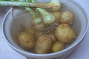 Potatoes and onions soaking in a bowl filled with water