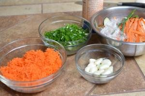 Ingredients on table include a bowl of grated carrots, sliced scallions, and peeled garlic