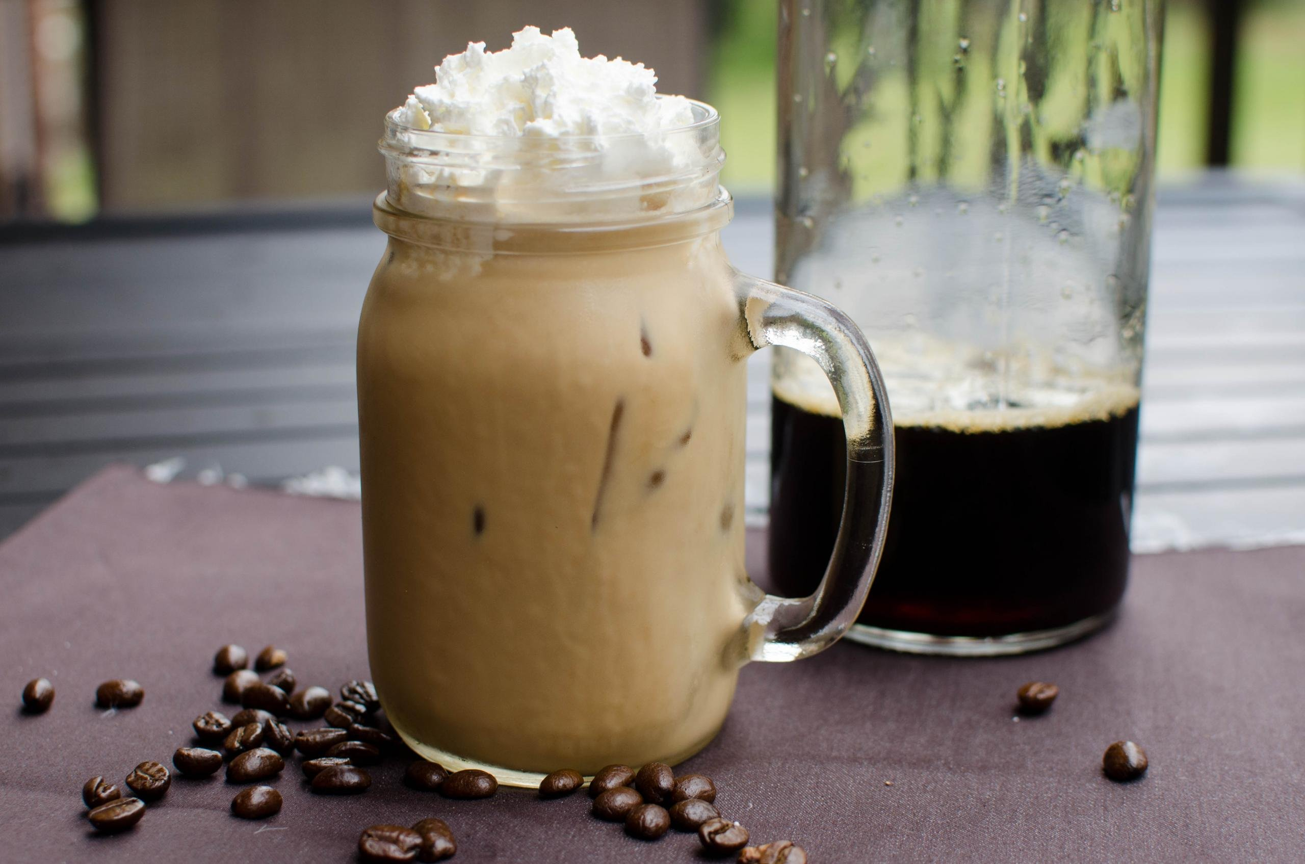 Cold-Brew Coffee in a mason jar cup with whipped cream on top and coffee beans around the bottom of the cup