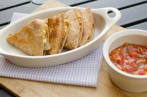 Breakfast Quesadillas in a bowl with salsa in a bowl besides them