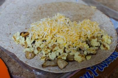 A tortilla with half of it layered with cheese, mushrooms, eggs and cheese again