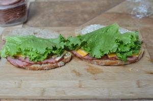 Each side of bread layered with meat, cheese and lettuce