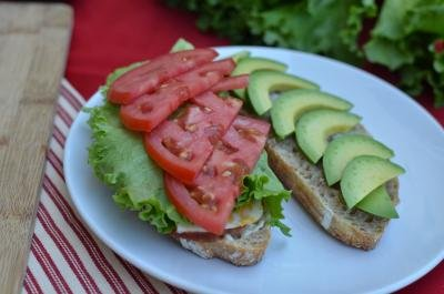 Garlic Toasted Sandwich halves with meat, cheese, lettuce, tomato, and avocado on a plate