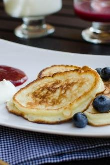 Russian Pancakes Oladi on a plate with blueberries, jam and sour cream