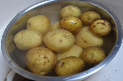 Unpeeled potatoes getting rinsed in a bowl