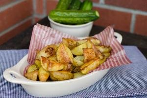 Ranch roasted potatoes in a serving bowl on a table with cucumbers in the background
