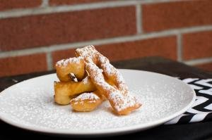 Angel Wing Cookies on a plate with powdered sugar sprinkled on top