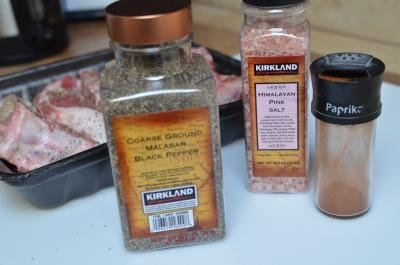 Spices on table including black pepper, salt and paprika with ribs in the back