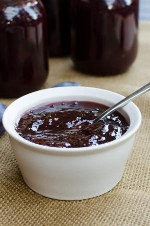 Prune Plum Jam in a bowl with a spoon and prunes around it, with jars behind the bowl