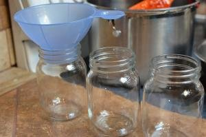 3 jars in a row with a funnel in one of the jars