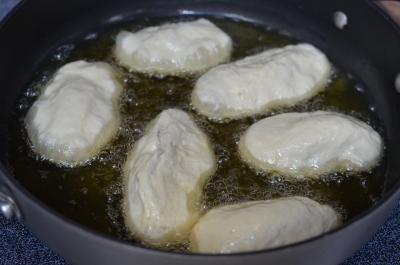 Overnight Piroshky frying in a skillet filled with oil