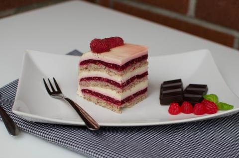 A slice of raspberry vanilla cream cake on a plate with a fork and chocolate squares next to it