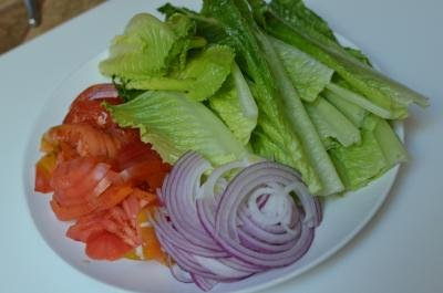 On a plate cut up tomatoes, purple onions and lettuce