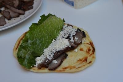Lamb meat sliced up on top of naan bread with feta on top and lettuce