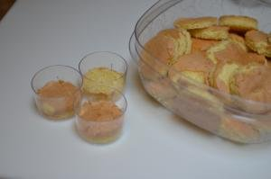 Sponge cake cut into small circles and placed into small cups and a container filled with them