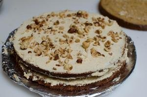 Sponge cake layer with cream and hazelnuts on top