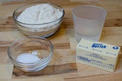 Ingredients on table including; stick of butte , water, salt and flour